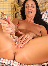 Brunette MILF stuffs her mature pussy with a big glass toy in here