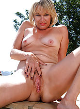 Sexy blonde MILF Tina poses naked outside by her pool